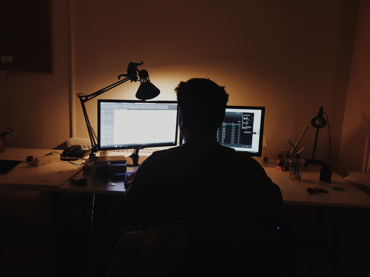 An image of a man sitting alone in a dark room, facing two computer screens.