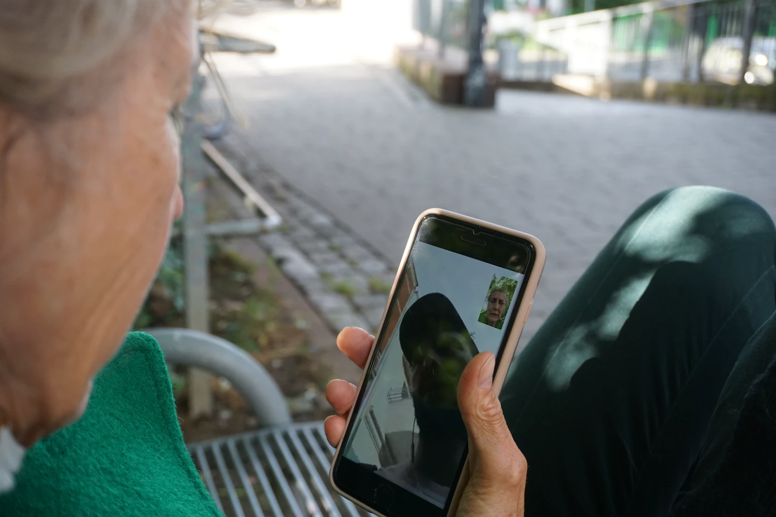An image of an old woman holding a phone in her hand. She is on a video call with a man in a baseball cap.