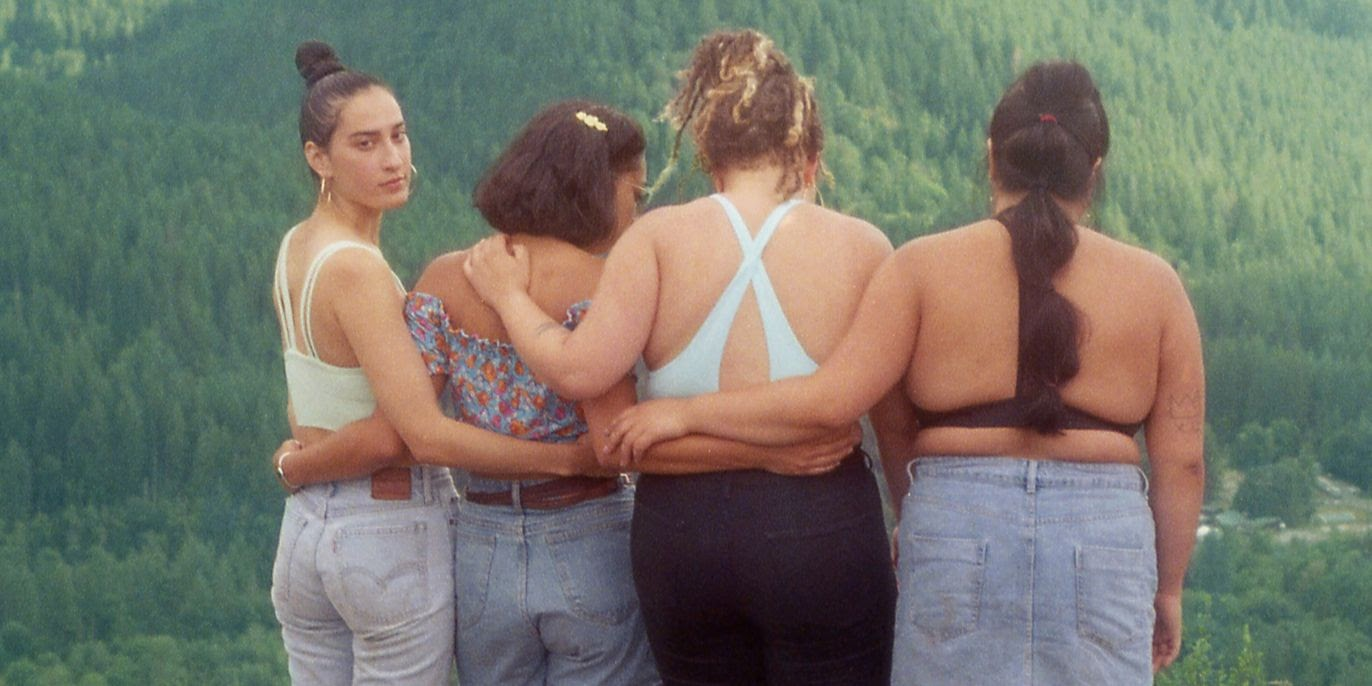 Four friends standing with their arms wrapped around each other. Three of them are looking at the mountains and one is looking behind them.