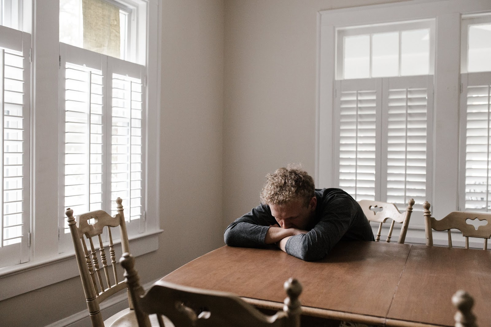 A disappointed man sitting at a dining room table with his head down.