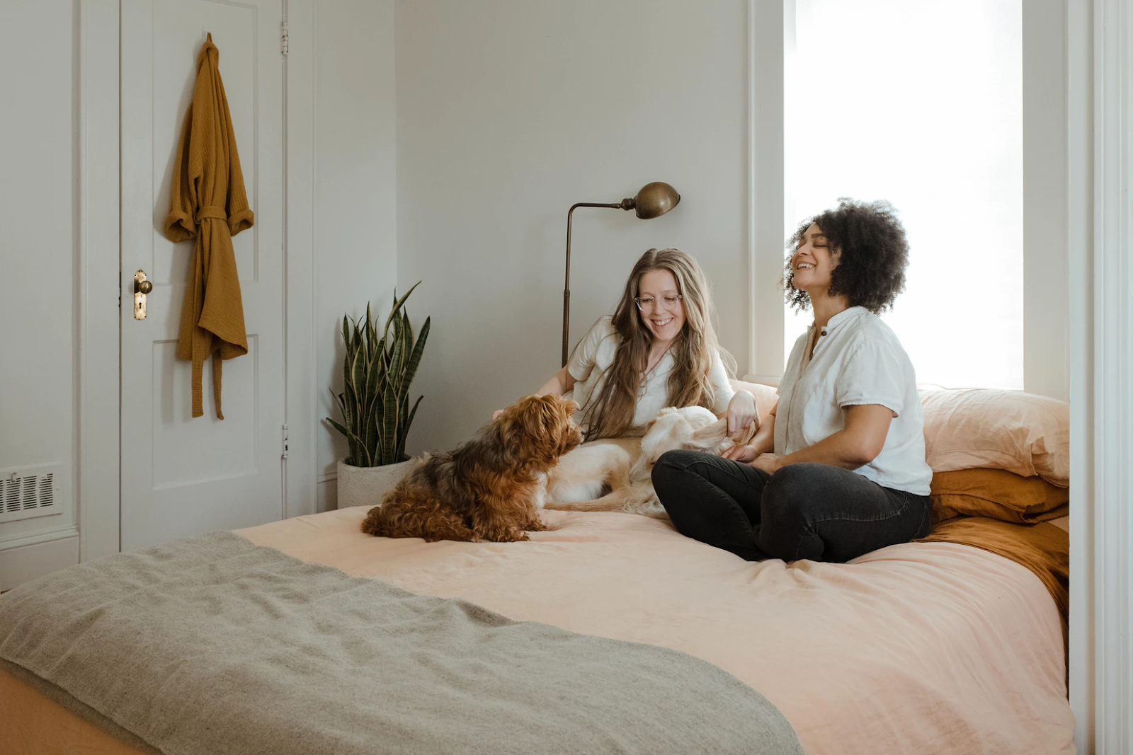 An image of two women sitting on a bed and laughing. One of them is petting a dog that sits beside them.