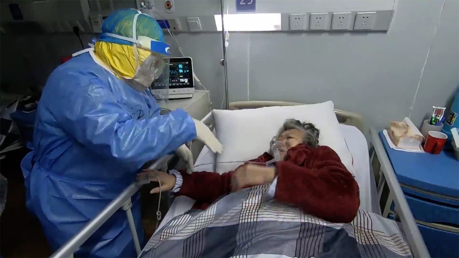 A health care worker wearing PPE gives aid to an elderly woman suffering from COVID-19.