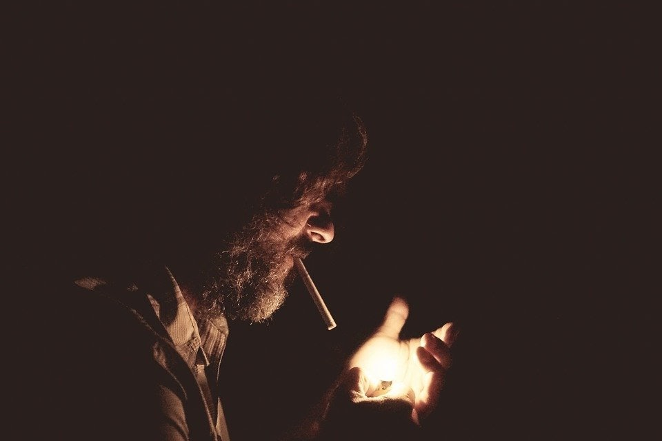 An image of the profile of a bearded man standing in the dark, holding a lighter in his hand to light the cigarette he's holding in his mouth.