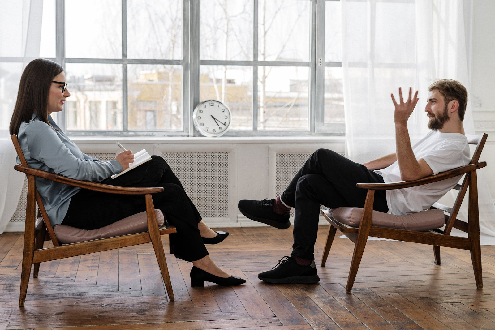 An image of two people in chairs sitting across from each other, with a clock balanced on the window between them. The woman is taking notes and listening as the man talks and gestures.