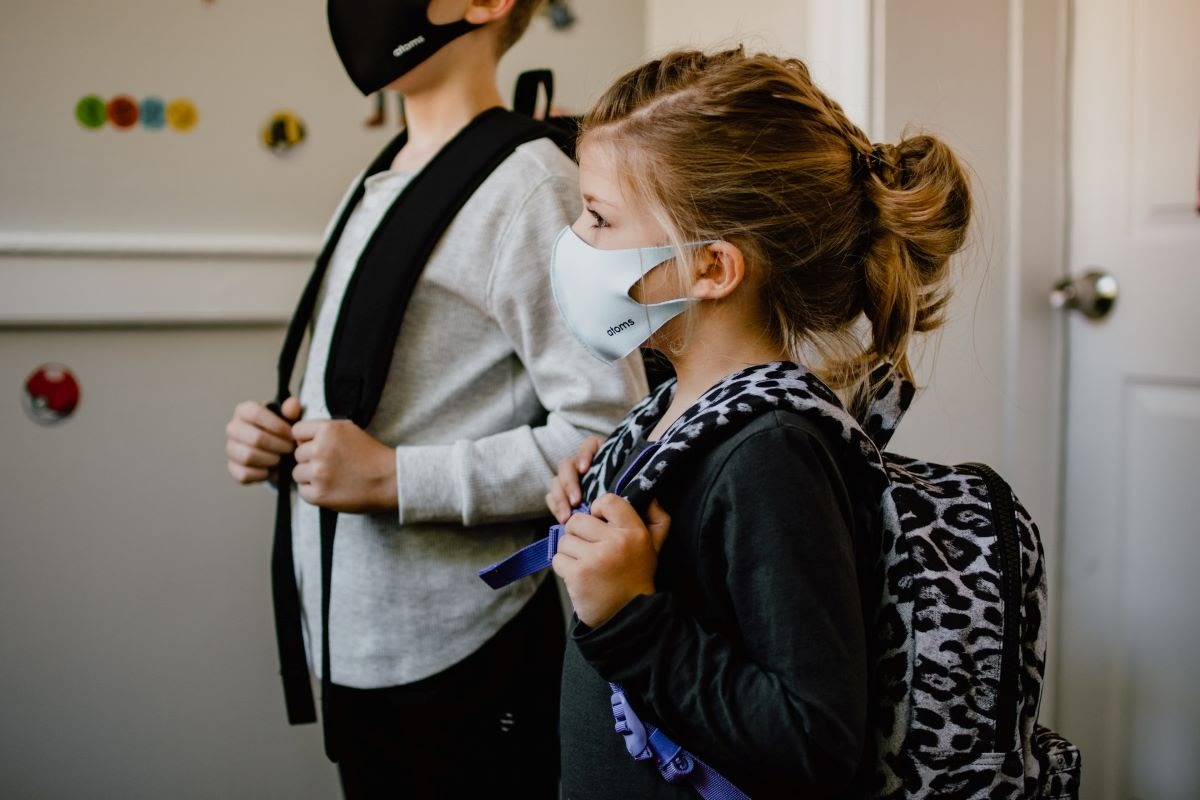 A pair of kids at school wearing masks