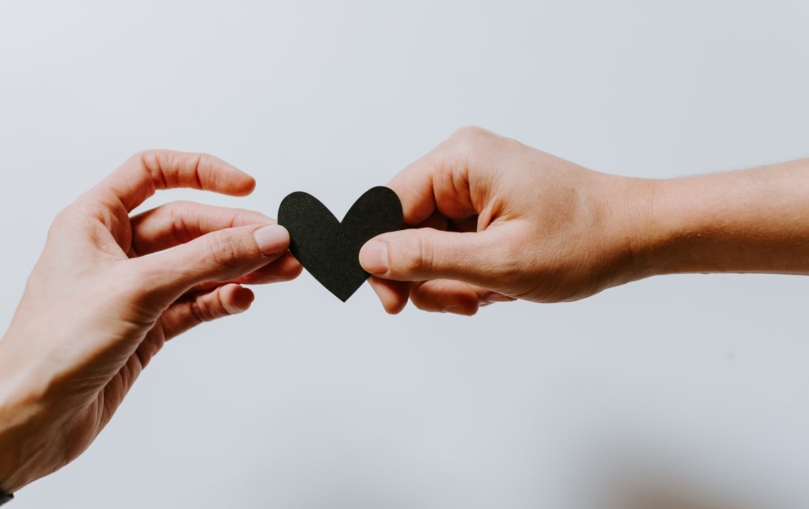 Two hands holding a paper heart.
