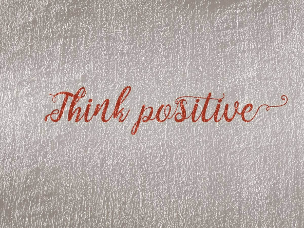"""Text """"Think Positive"""" Written in Cursive on Paper"""