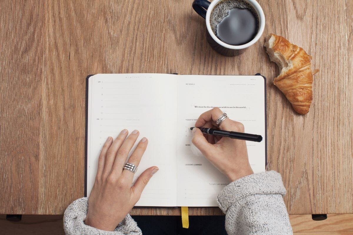 Woman Writing in a Planner With Coffee and a Croissant