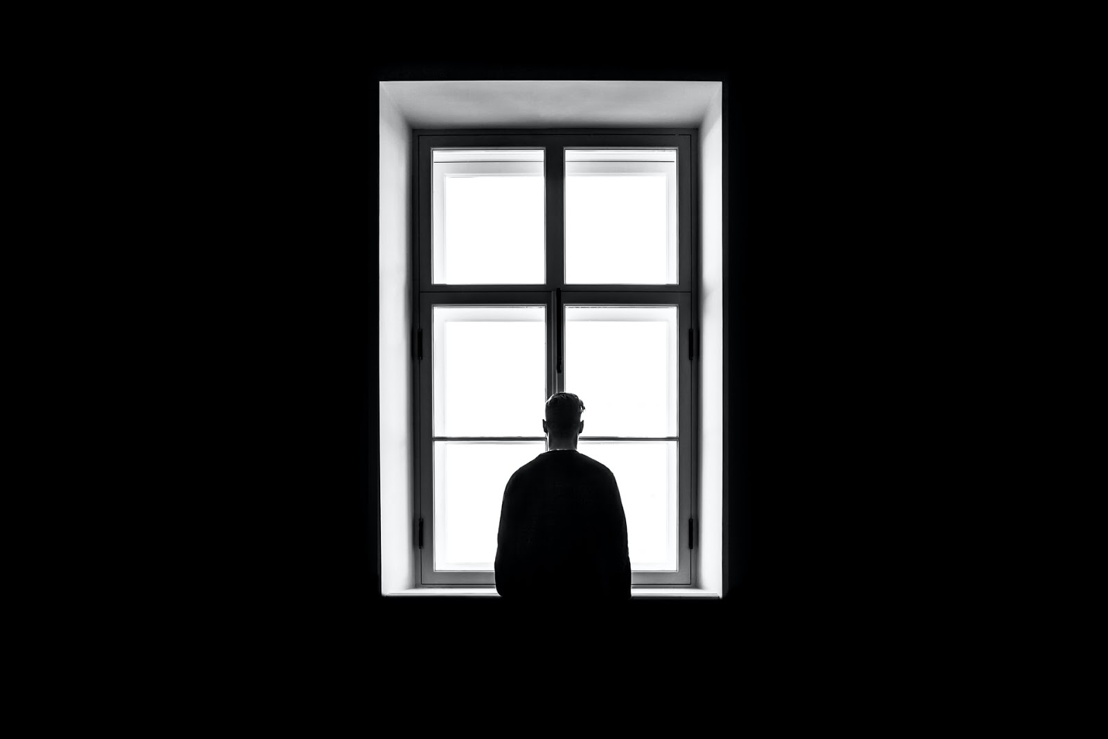 A man looking out a window symbolizing being alone.