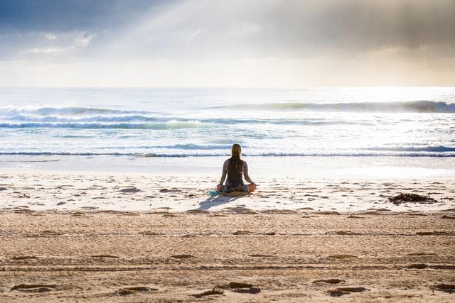 A Woman Meditating on a Beach
