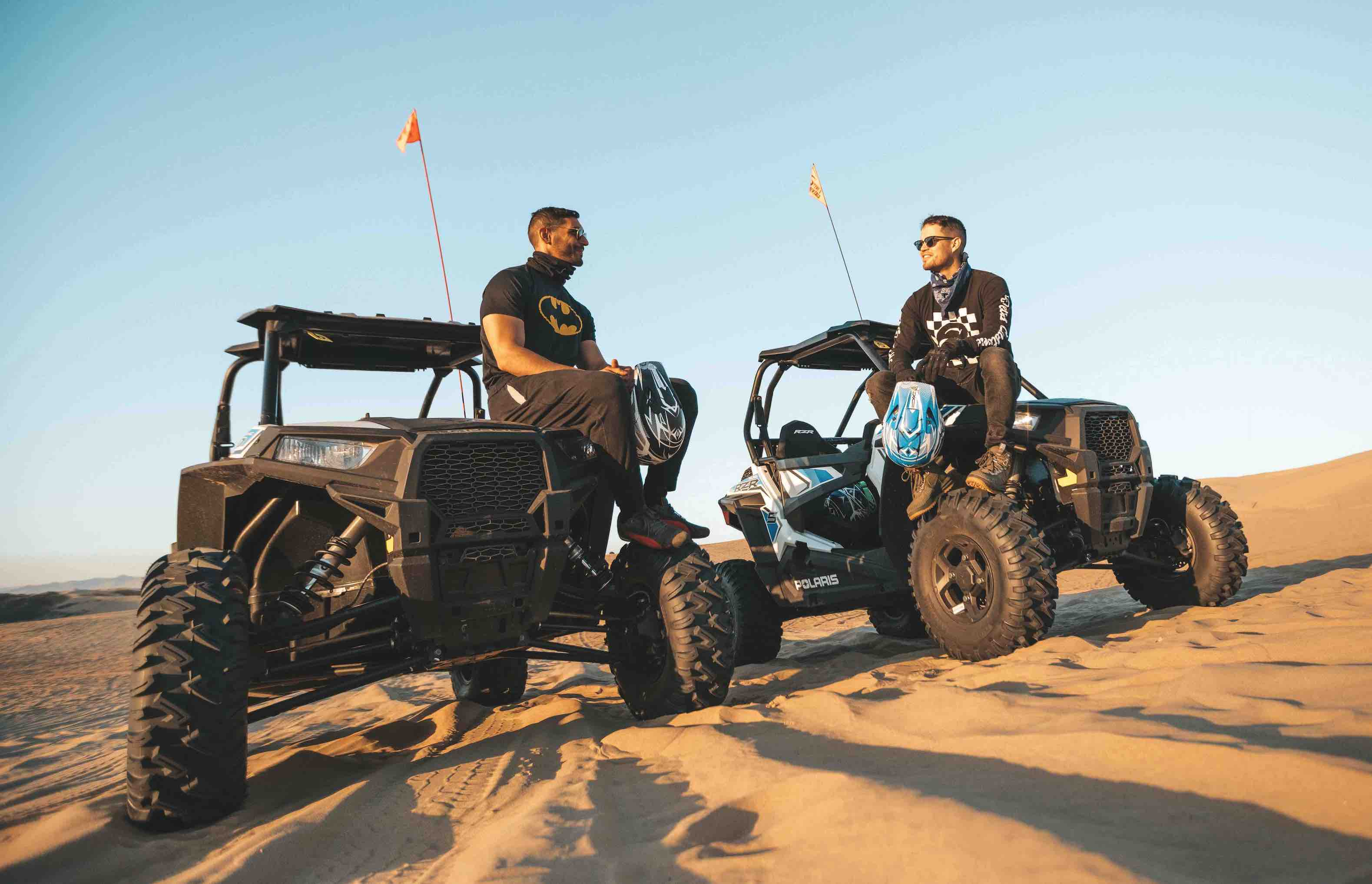 2 dune buggies in the desert with a man sitting on each hood of both buggies.