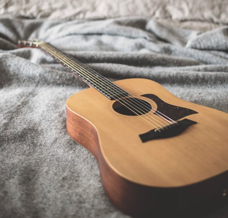 Acoustic guitar sitting on a bed.