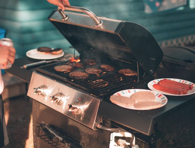 Meat being barbecued outdoors.