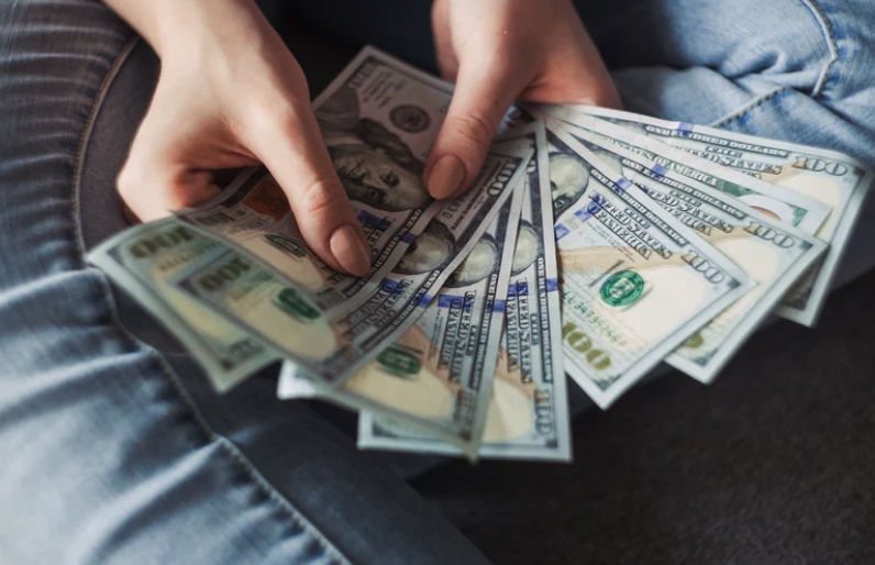 Woman's hands holding 8, one hundred dollar bills fanned out.