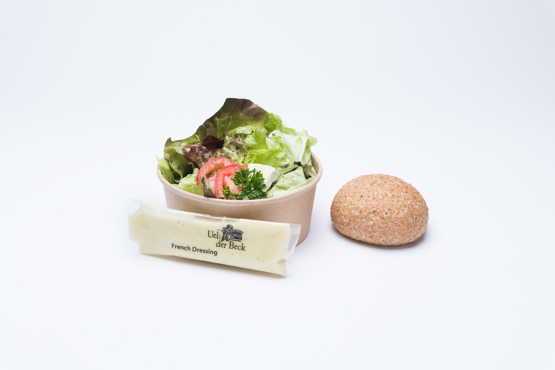 Grüner Salat mit einem Vollkornbrötchen und französische Salatsauce