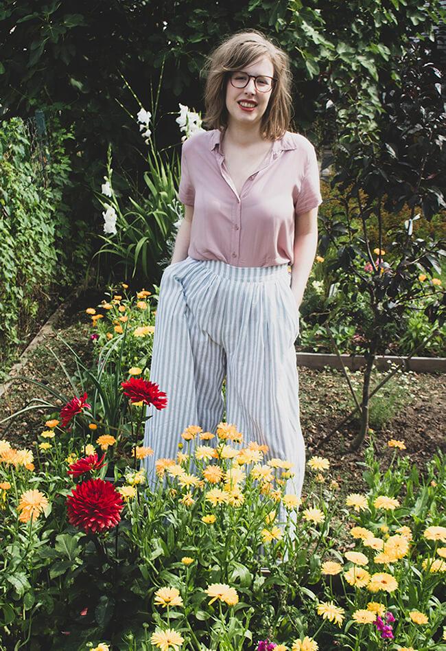 Foto van Sarah. Ze is blank en heeft blond haar tot schouderlengte. Ze draagt een bruine grote bril. Ze staat in een tuin en lacht naar de camera. Er groeien bloemen in geel en rood voor haar, op de achtergrond, een appelboompje, nog meer bloemen en in de verte zie je witte gladiolen. Ze draagt een roze hemd met korte mouwen en een broek met hoge taille. De broek is wit met lichtblauwe strepen. Een erg geslaagde combinatie.