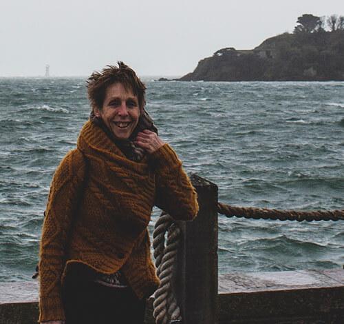 foto van Jatte. Ze is blank, heeft vrij kort, opstekend haar en lacht naar de camera. Ze draagt een gele wolle  gebreide trui en een bruine sjaal. Ze staat aan zee, je ziet een eiland achter haar. Het is koud, de zee is wild en het waait want ze houd haar sjaal en vest met een hand vast tegen de wind.