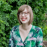 An image of Sarah, she looks super cool in a green and pink jumpsuit with a leafy print, she wears large glasses, has medium length (real!) blond hair and is standing in front of a large green shrub