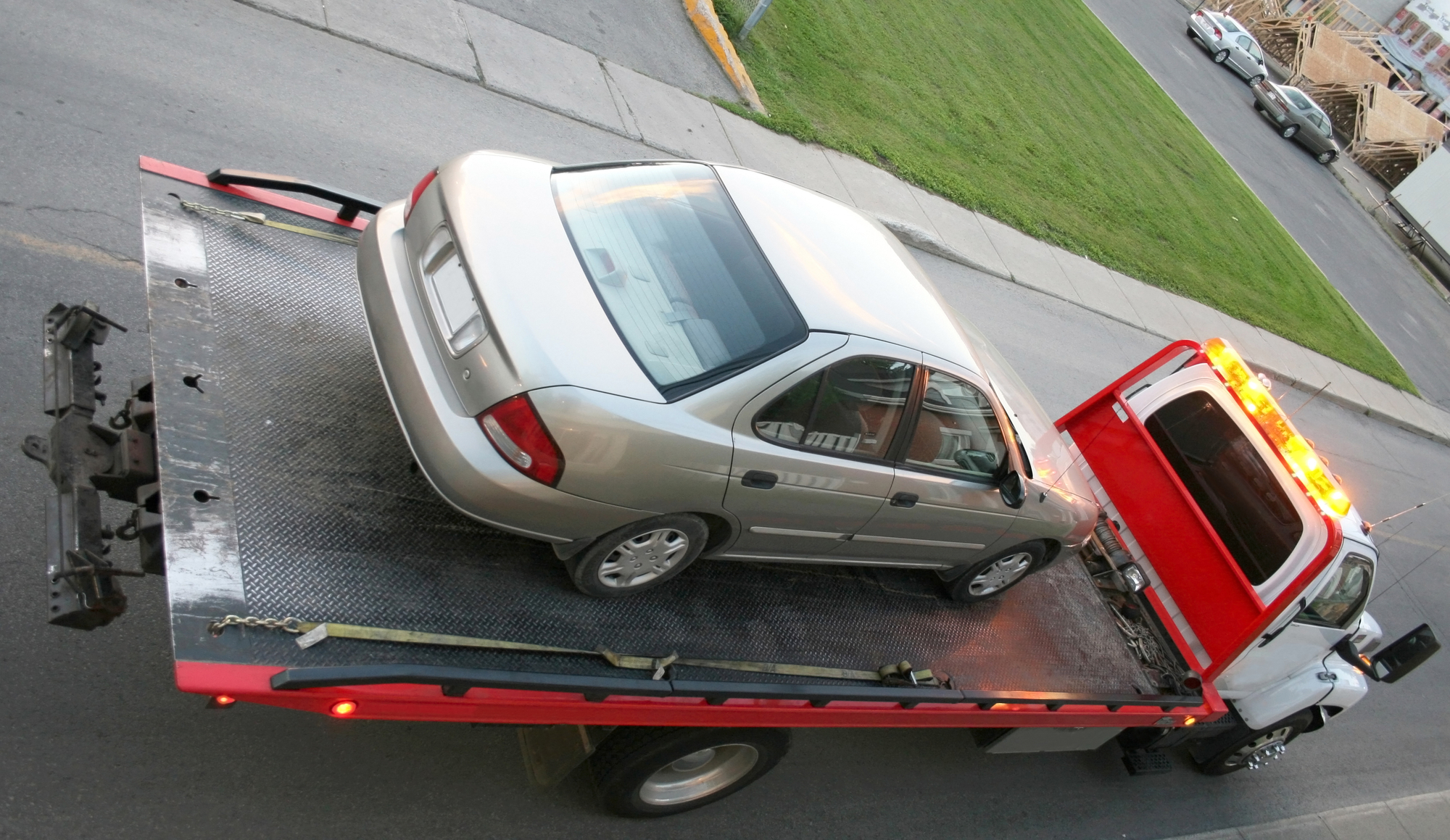 A car being hauled on a flatbed truck