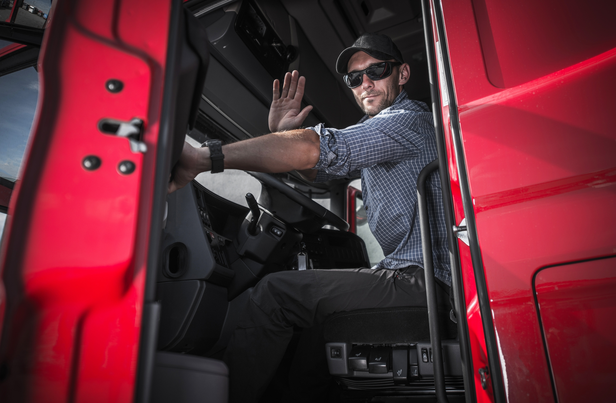 A truck driver waves from the driver seat