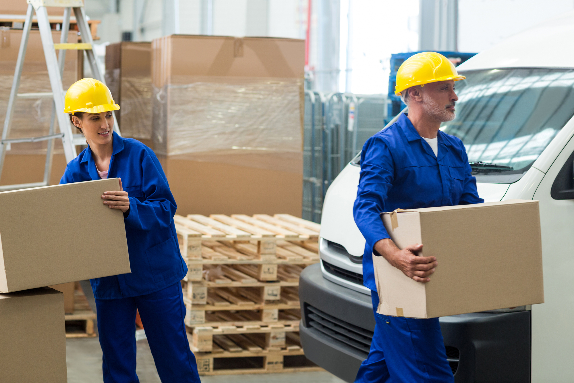 Two workers lift packages on the loading dock