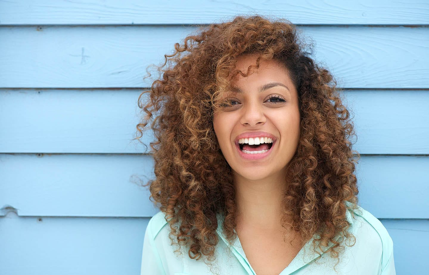 girl with curly hair smiling against blue wall