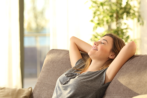 woman enjoying clean air in her home