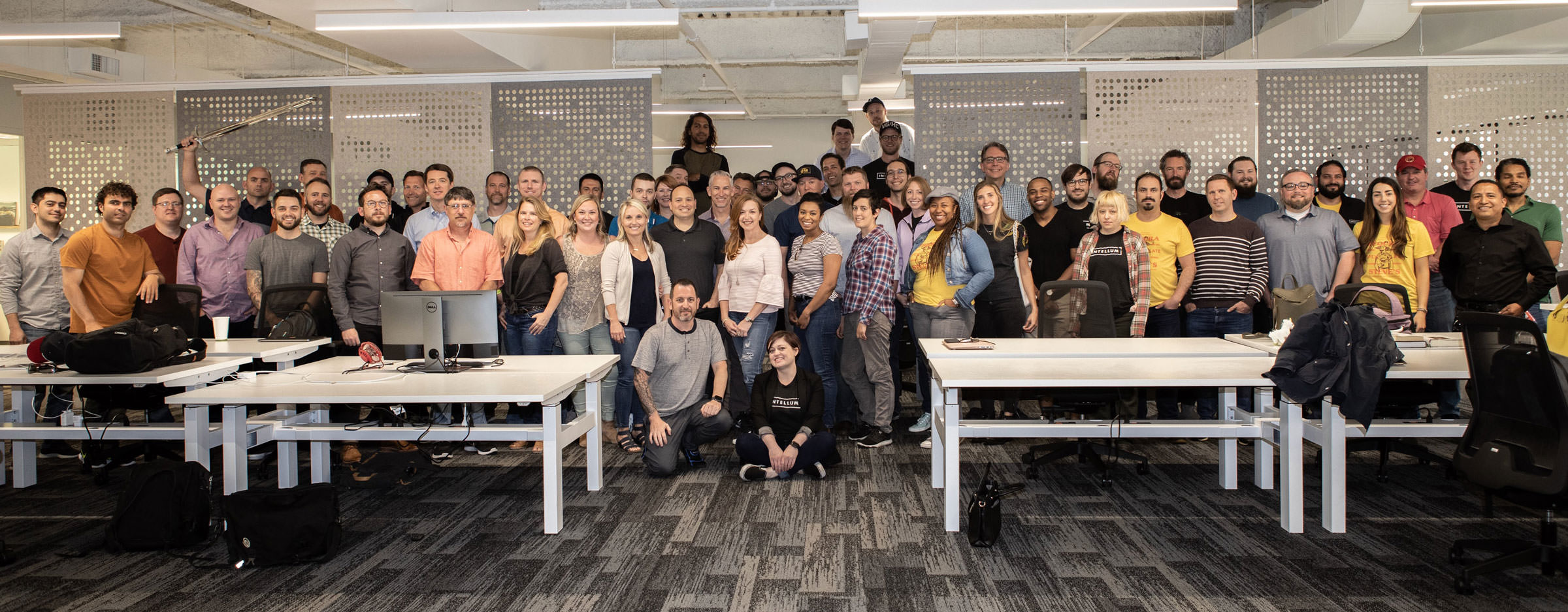 A wide shot of all Intellum employees posing for a group photo in the Intellum office