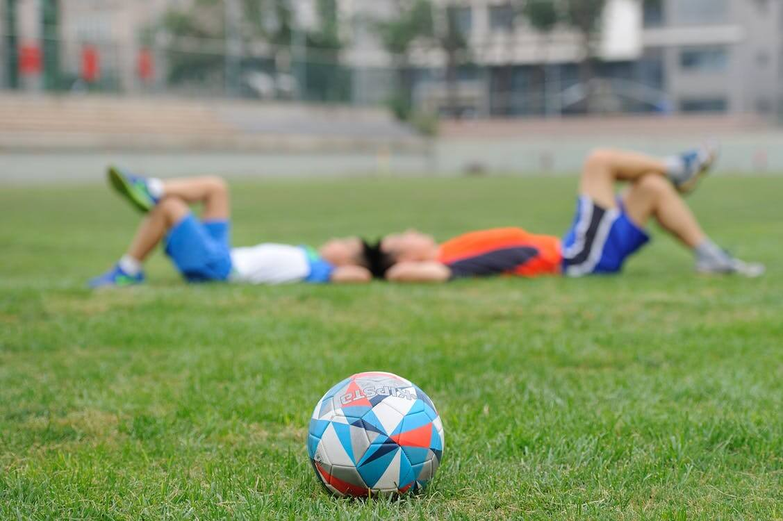 boys laying head to head, soccer ball