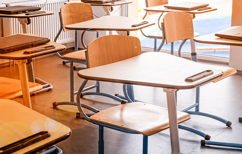 Series of modern wooden desks in an empty classroom - Neovation Learning Solutions