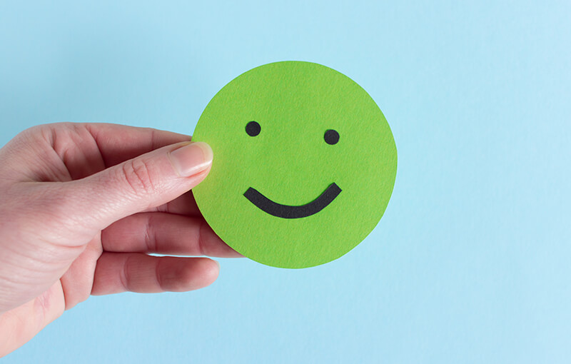 A hand holding a green paper circle with a happy face drawn on it.