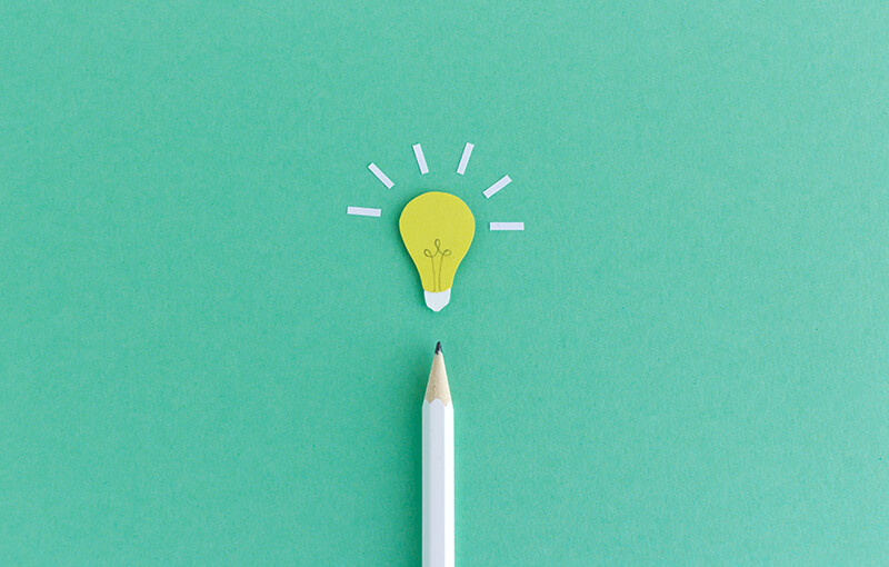 A white pencil, pointing to the top of the photo, resting on a seafoam green background. At the tip of the pencil is a paper light bulb cutout.