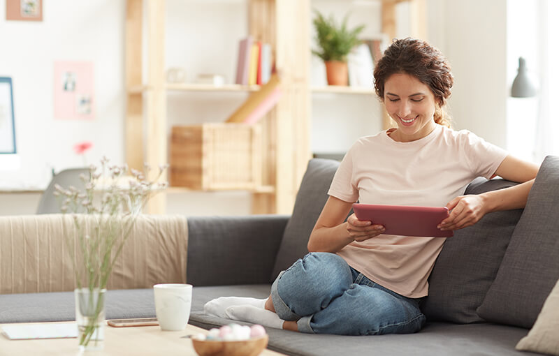 A smiling woman sitting on a couch and looking at a tablet with her legs folded up under her.
