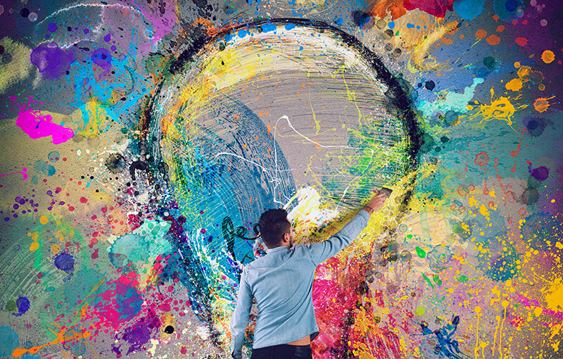 Man painting a large lightulb on the side of a wall. The wall is covered in colorful paint splatters.