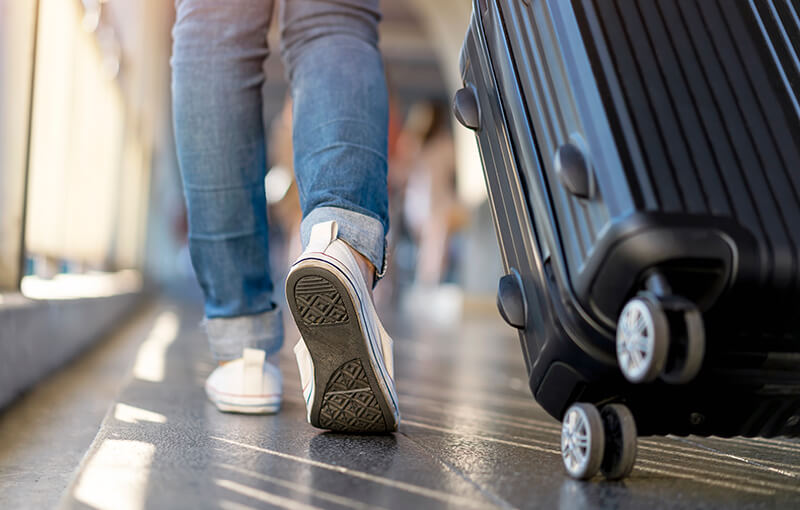 Close-up on the back of a person's legs and feet, wearing white sneakers, as they walk away, wheeling a black suitcase behind them.