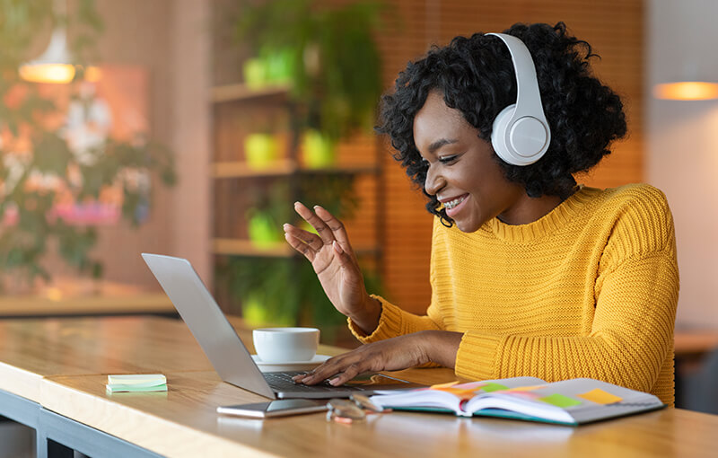 Woman with curly black hair in white headphones waving at her laptop screen.