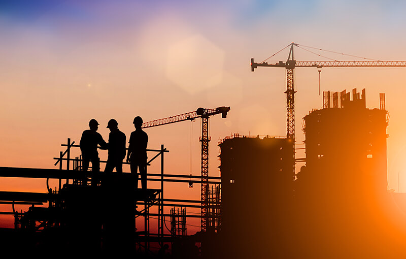 Three construction workers in front of cranes and scaffolding, silhouetted against a sunset.