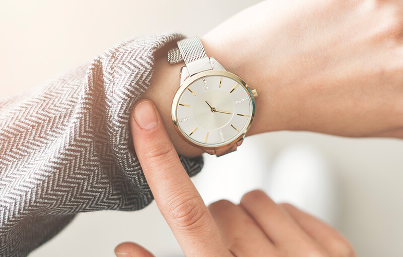 Close-up of a wristwatch on a person's arm. They're pulling back their shirt sleeve to expose the watch face.