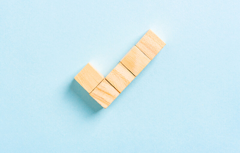 A checkmark made out of 5 wooden cubes.