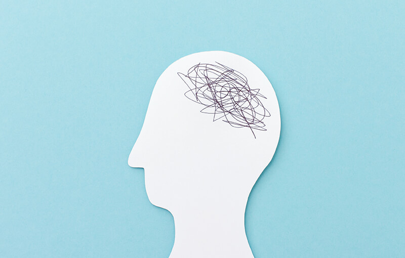 Paper cut out of the shape of a person's profile with the area where the brain would be covered in black scribbles.