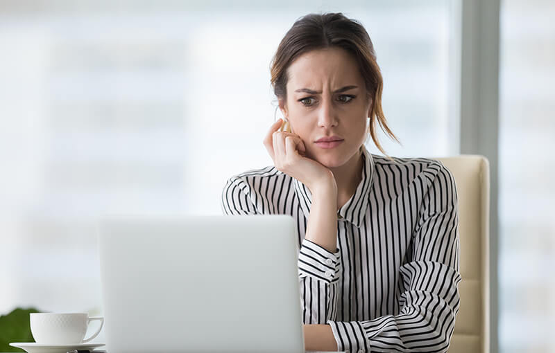 A woman in a black and white, vertically striped shirt with her head resting in her hand. She's looking at her laptop which is directly in front of her, with a confused expression on her face.