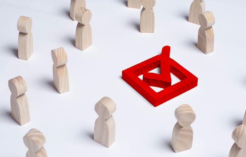 Wooden figures representing people are scattered, forming a ragged circle around a wooden red box with a wooden red checkmark in it.