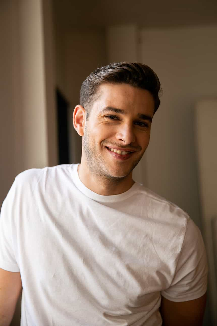 Man with styled brown hair in white t-shirt smiling
