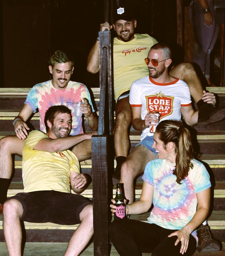 Four gay guys and one lesbian wearing queer T-shirts.