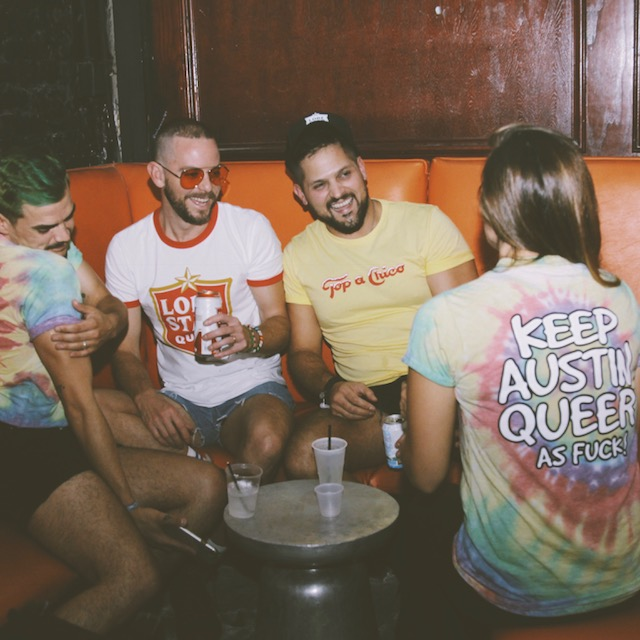 Group of young queer folk enjoying themselves in a bar lounge.