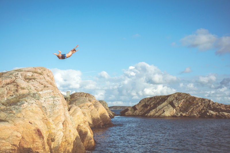 a man taking a leap of faith off a rock into the ocean