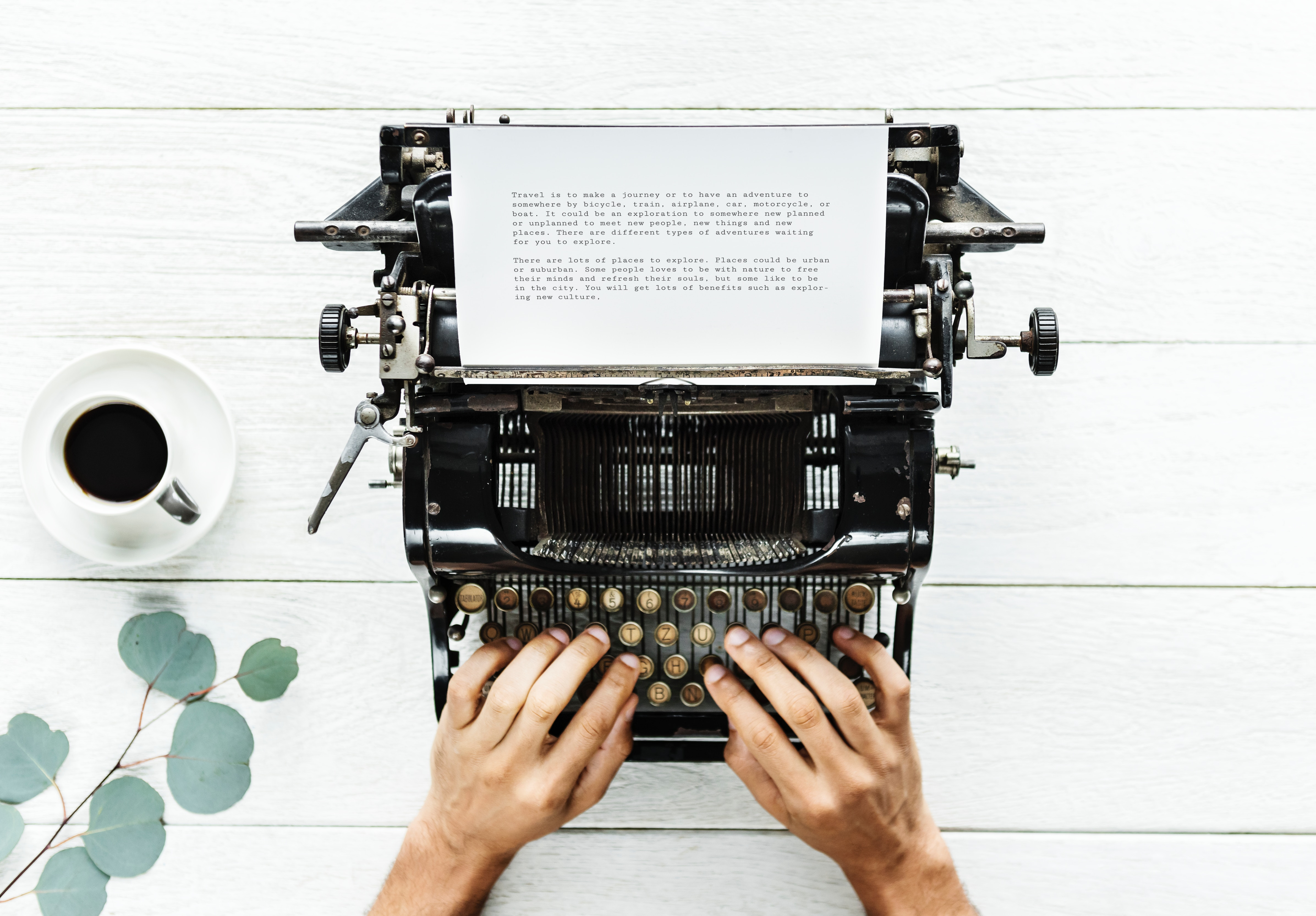 person typing story on typewriter on white table with plant