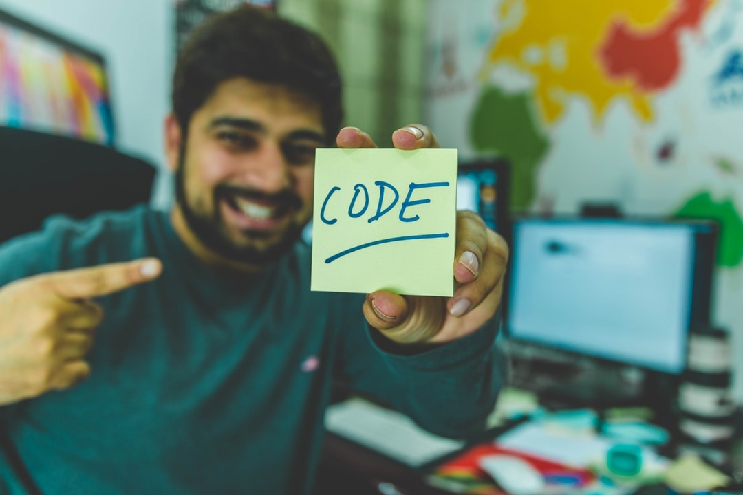 developer smiling and holding up sticky note that says code