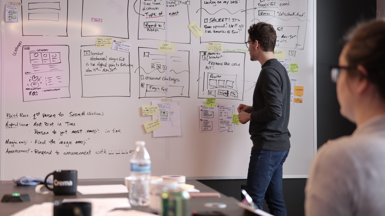 designer sean in design sprint explaining something in front of white board
