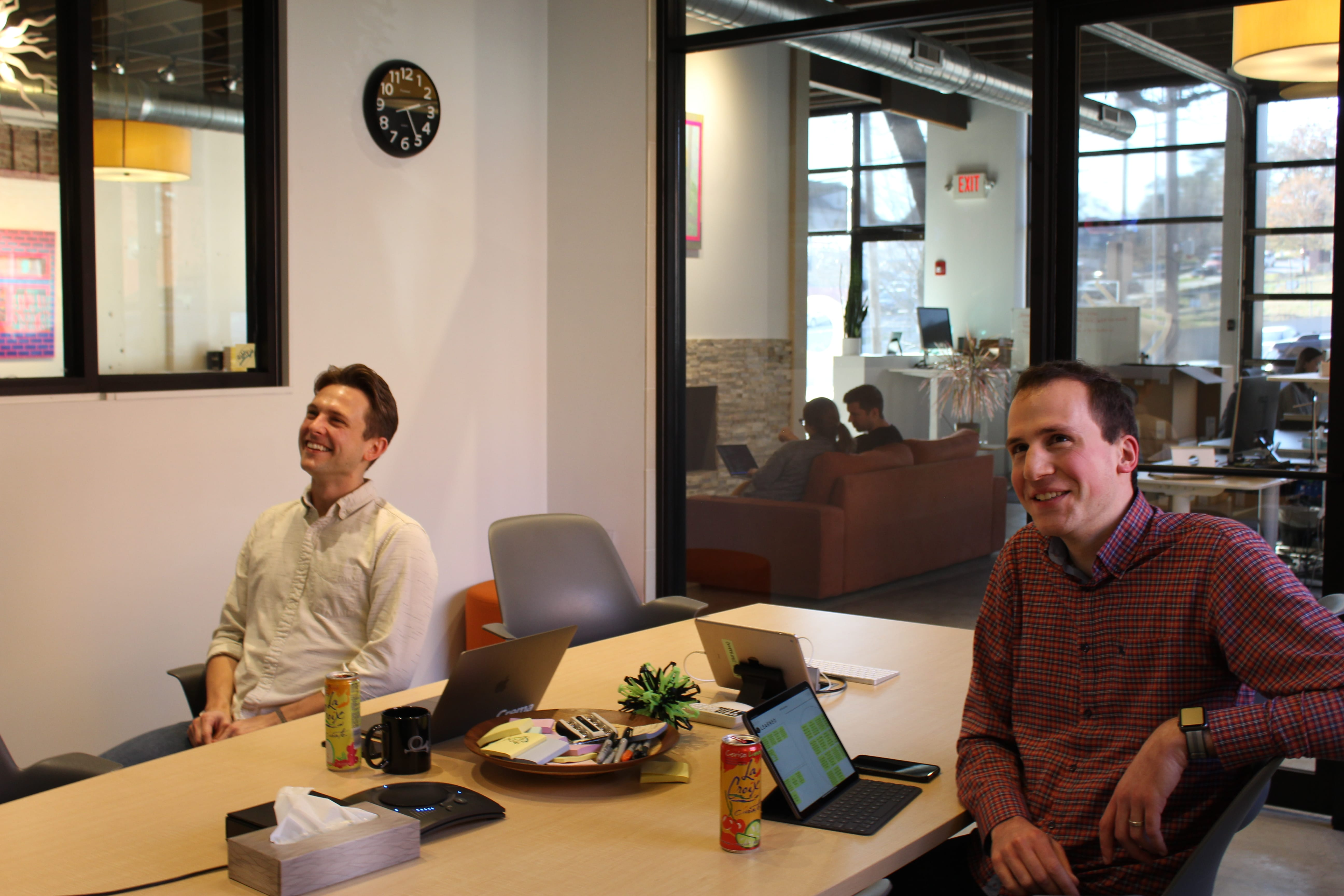 product managers in room smiling during meeting